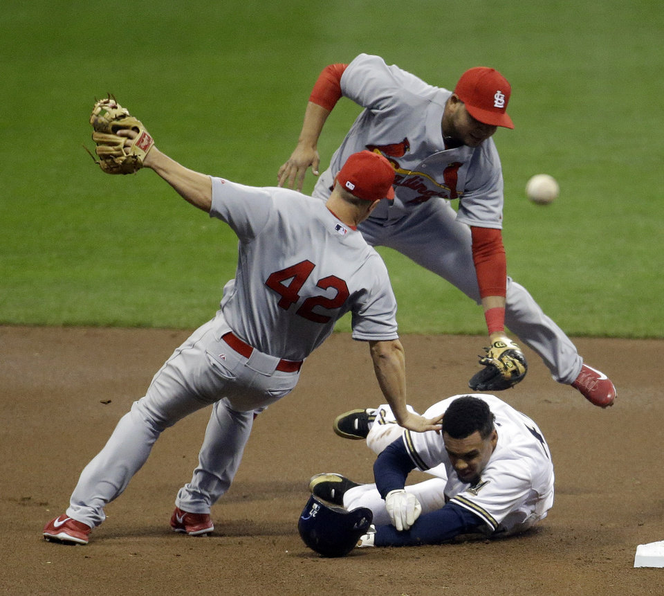 Photo - Milwaukee Brewers' Carlos Gomez is out at second after St. Louis Cardinals' Mark Ellis, left, and Jhonny Peralta turn a double play on a ball hit by Ryan Braun during the first inning of a baseball game Tuesday, April 15, 2014, in Milwaukee. (AP Photo/Morry Gash)