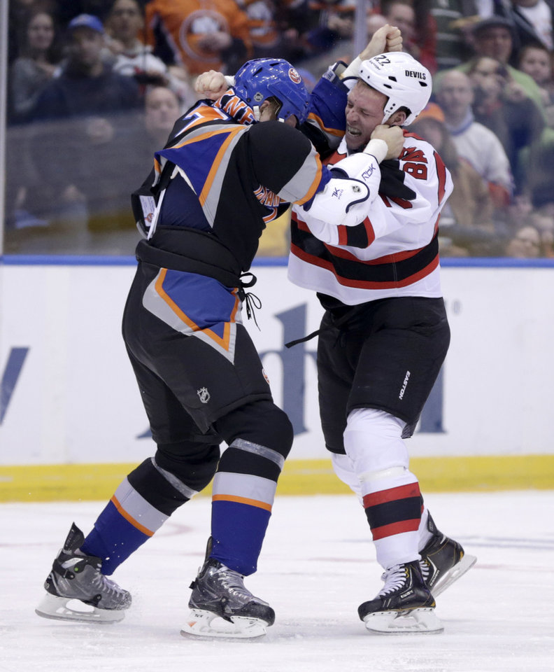 New Jersey Devils' Krys Barch, right, and New York Islanders' Matt Carkner fight during the second period of the NHL hockey game on Sunday, Feb. 3, 2013, in Uniondale, N.Y. (AP Photo/Seth Wenig)