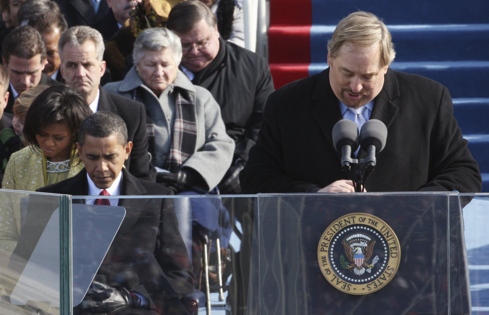 Photo - The Rev. Rick Warren, of the Saddleback Church in Lake Forest, Calif., gives the invocation as President-elect Barack Obama and his wife, Michelle, left, bow their heads during swearing-in ceremonies at the U.S. Capitol in Washington, Tuesday, Jan. 20, 2009.  (AP Photo/Ron Edmonds)