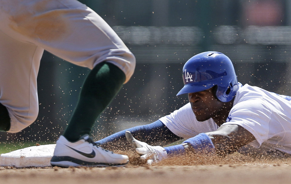 Photo - Los Angeles Dodgers' Yasiel Puig, right, steals second base under the legs of Oakland Athletics second baseman Adam Rosales during the third inning of a spring training baseball game on Tuesday, March 19, 2013 in Glendale, Ariz. (AP Photo/Marcio Jose Sanchez)
