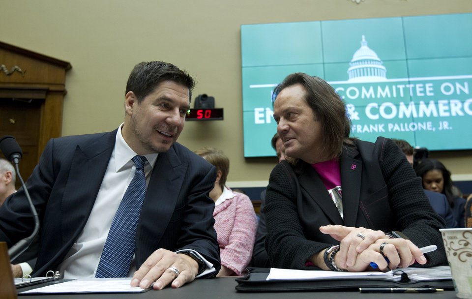 Photo -  FILE - In this Feb. 13, 2019, file photo Sprint Corporation Executive Chairman Marcelo Claure, left, speaks with T-Mobile US CEO and President John Legere during the House Commerce subcommittee hearing on Capitol Hill in Washington. A federal judge has removed a major obstacle to T-Mobile's $26.5 billion takeover of Sprint, as he rejected claims by a group of states that the deal would mean less competition and higher phone bills. (AP Photo/Jose Luis Magana, File)