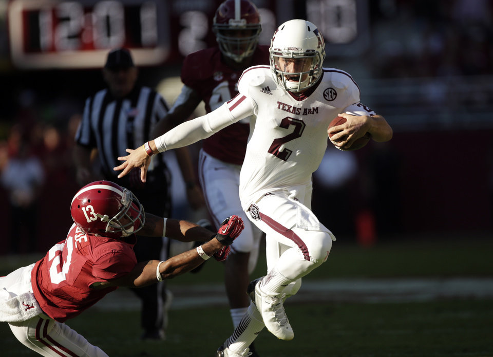 Photo -   Texas A&M quarterback Johnny Manziel (2) runs through the tackle of Alabama defensive back Deion Belue (13) during the first half of an NCAA college football game at Bryant-Denny Stadium in Tuscaloosa, Ala., Saturday, Nov. 10, 2012. (AP Photo/Dave Martin)