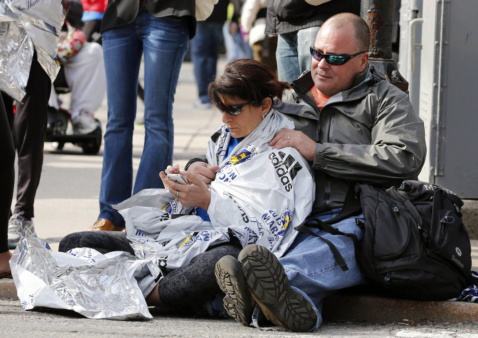 Chris Darmody, right, holds his wife Sue in Boston, Monday, April 15, 2013. Chris says he was waiting for Sue when an explosion detonated near his location at the finish line of the Boston Marathon. The couple were later reunited after all runners were diverted from the course. (AP Photo/Michael Dwyer) ORG XMIT: MAMD110
