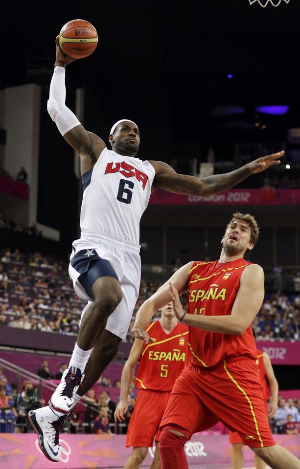 United States' LeBron James dunks over Spain's Sergio Llull during a men's gold medal basketball game at the 2012 Summer Olympics, Sunday, Aug. 12, 2012, in London. (AP Photo/Eric Gay)