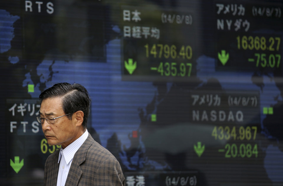 Photo - A man walks past an electronic stock board of a securities firm in Tokyo as the 225-issue Nikkei Stock Average, shown top center, dived 454.00 points, or 2.98 percent, and finished at 14,778.37, hitting a two-month low Friday, Aug. 8, 2014. Asian stocks sank Friday as jitters over the crises in Iraq and Ukraine escalated but Chinese stocks rose after trade figures showed surprisingly strong growth in exports. (AP Photo/Eugene Hoshiko)
