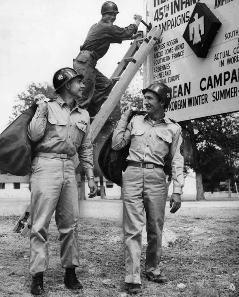 Photo - Another camp is past-another bit of history for the history making Thunderbird division as Sfc. Walter K. Cassady starts taking down the famed 45th division sign at North Fort Hood, as the division heads for home Sunday.  Waiting for their time to shove off are M-Sgt. John W. Ogle, left and Sfc. Elmer C. Kelley, both of Midwest City and both in the 45th Signal company.  Staff photo by Richard Cobb.  Photo undated and published on 08/19/1956 in The Daily Oklahoman.
