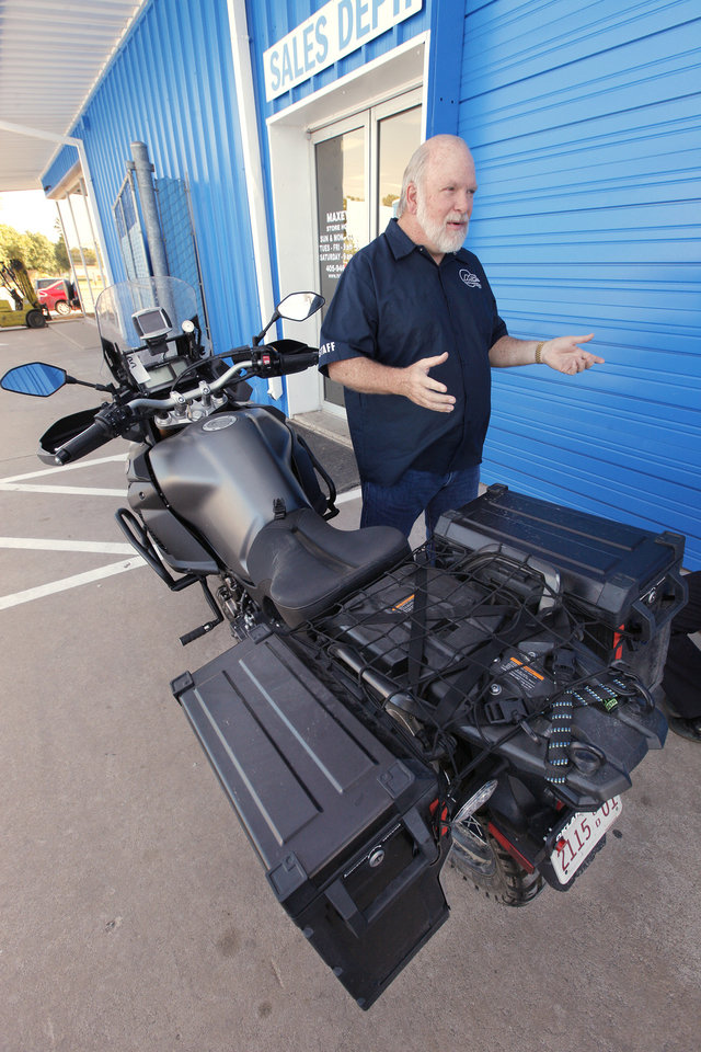 Photo -  Dan Maxey talks about his ride to Alaska on the Yamaha Super Tenere motorcycle parked outside his shop in Oklahoma City on Tuesday. Photo by Paul B. Southerland, The Oklahoman   PAUL B. SOUTHERLAND -  PAUL B. SOUTHERLAND