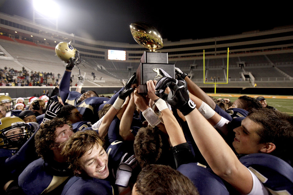 Photo - Heritage Hall celebrates with the trophy after winning the Class 3A high school football state championship game 28-21 against Kingfisher at Boone Pickens Stadium in Stillwater, Okla., Friday, December 10, 2010. By Bryan Terry, The Oklahoman