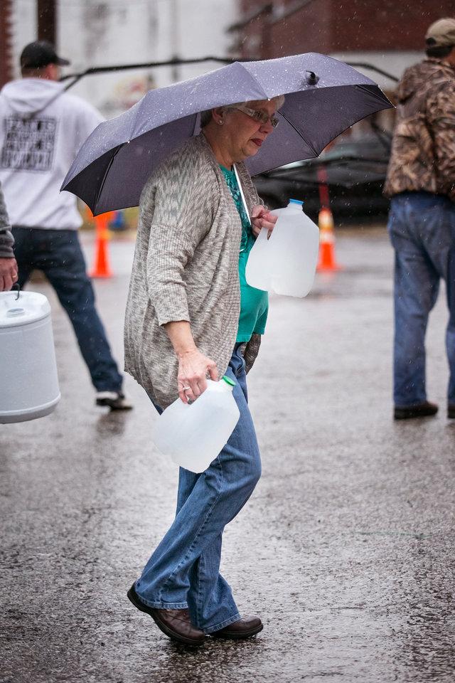 Photo - Local residents in Kanawha County, W.V., flocked to distribution centers to load up on bottled water Saturday, Jan. 11, 2014 in Charleston, W.V. About 300,000 people in nine counties entered their third day Saturday without being able to drink, bathe in, or wash dishes or clothes with their tap water after a foaming agent escaped the Freedom Industries plant in Charleston and seeped into the Elk River. (AP Photo Michael Switzer)