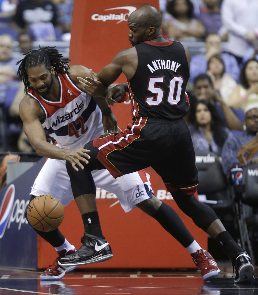 Photo - Washington Wizards forward Nene, left, of Brazil, and Miami Heat forward Joel Anthony scramble for the ball during the first half of an NBA basketball game Wednesday, April 10, 2013, in Washington.  (AP Photo/Evan Vucci)