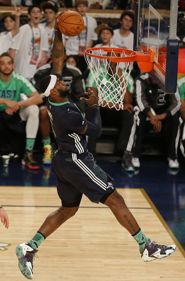 Photo - East Team's LeBron James, of the Miami Heat (6) dunks the ball against the West Team during the NBA All Star basketball game, Sunday, Feb. 16, 2014, in New Orleans. (AP Photo/Bill Haber)