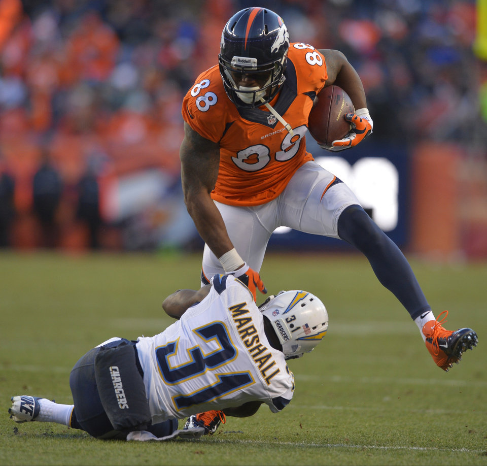 Photo - Denver Broncos wide receiver Demaryius Thomas (88) steps over San Diego Chargers cornerback Richard Marshall in the third quarter of an NFL AFC division playoff football game, Sunday, Jan. 12, 2014, in Denver. (AP Photo/Jack Dempsey)