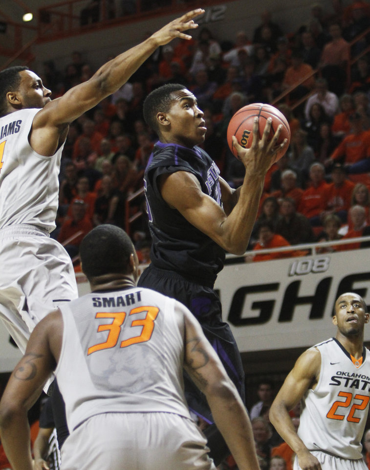Photo - Kansas State forward Wesley Iwundu, center, shoots a layup over Oklahoma State defenders Brian Williams, left, and Marcus Smart (33) during an NCAA college basketball game in Stillwater, Okla., Monday, March 3, 2014. Oklahoma State won 77-61. (AP Photo/The Oklahoman, KT King)