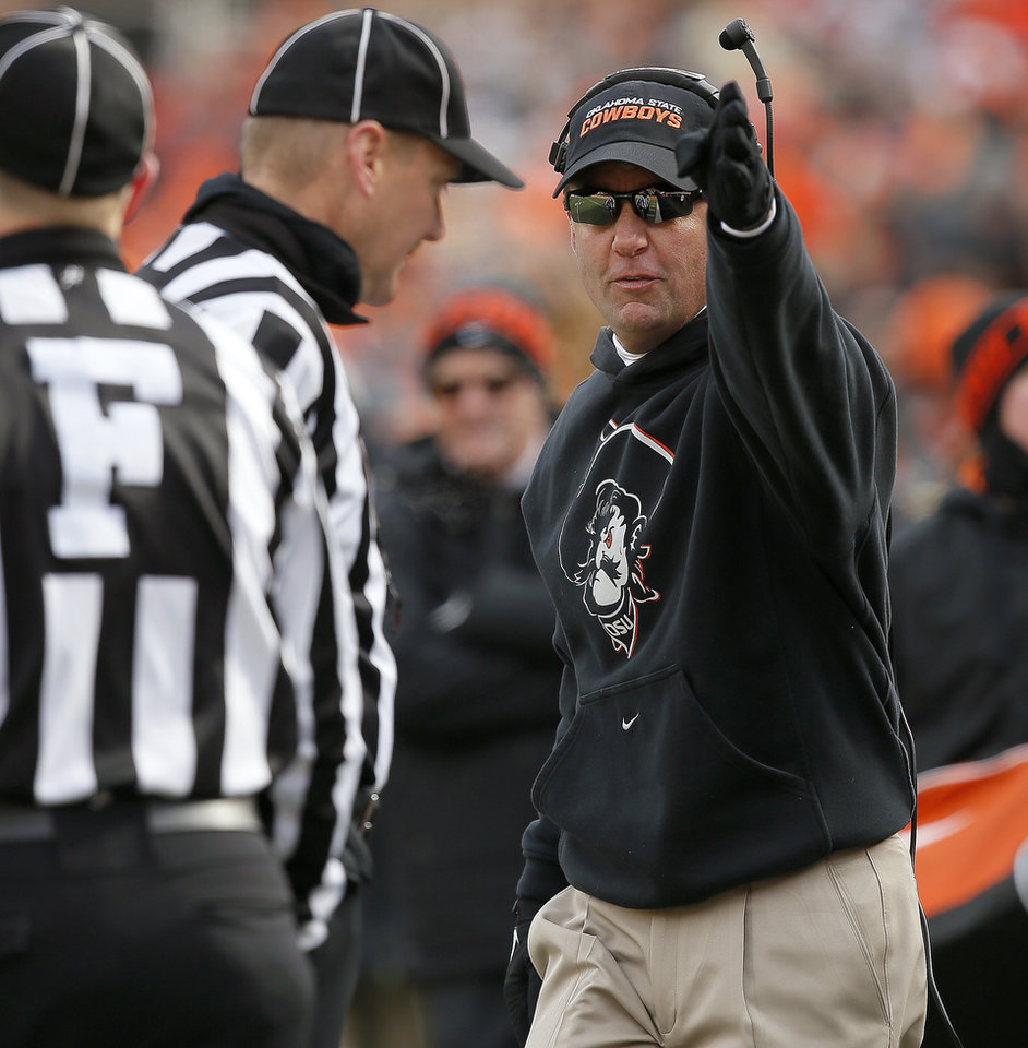Photo - Oklahoma State coach Mike Gundy argues with an official during the Bedlam college football game between the Oklahoma State University Cowboys (OSU) and the University of Oklahoma Sooners (OU) at Boone Pickens Stadium in Stillwater, Okla., Saturday, Dec. 7, 2013. Oklahoma won 33-24. Photo by Bryan Terry, The Oklahoman
