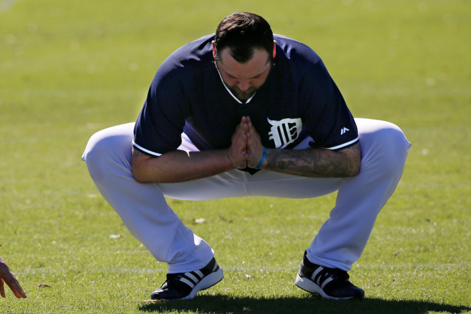 Photo - Detroit Tigers pitcher Joba Chamberlain stretches during the team's first day of baseball spring training for pitchers and catchers, in Lakeland, Fla., Friday, Feb. 14, 2014. (AP Photo/Gene J. Puskar)