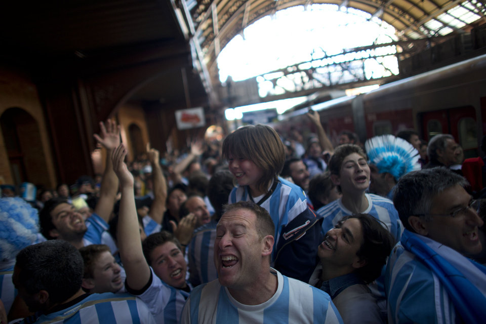 Photo - Argentine soccer fans, decked out in their team's colors, sing and cheer as they wait to be transported to the Itaquerao Stadium where Argentina faces Switzerland in their second round World Cup match, in Sao Paulo, Brazil, Tuesday, July 1, 2014. Argentina went on to defeat Switzerland 1-0 in extra time to advance to the quarterfinals. (AP Photo/Dario Lopez-Mills)