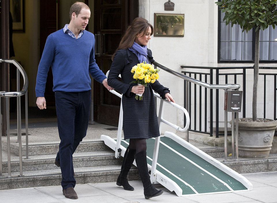 FILE- In this Thursday, Dec. 6, 2012 file photo, Britain\'s Prince William stand next to his wife Kate, Duchess of Cambridge as she leaves the King Edward VII hospital in central London. Prince William and his wife Kate are expecting their first child, and the Duchess of Cambridge was admitted to hospital suffering from a severe form of morning sickness in the early stages of her pregnancy. King Edward VII hospital says a nurse involved in a prank telephone call to elicit information about the Duchess of Cambridge has died. The hospital said Friday, Dec. 7, 2012 that Jacintha Saldanha had been a victim of the call made by two Australian radio disc jockeys. They did not immediately say what role she played in the call. (AP Photo/Alastair Grant, File)