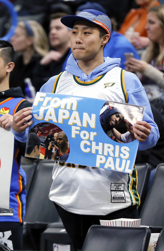 "Photo - Masaki Miyao, 24, from Tokyo, holds a sign that reads ""From Japan for Chris Paul"" before an NBA basketball game between the Oklahoma City Thunder and Chicago Bulls at Chesapeake Energy Arena in Oklahoma City, Monday, Dec. 16, 2019. [Nate Billings/The Oklahoman]"