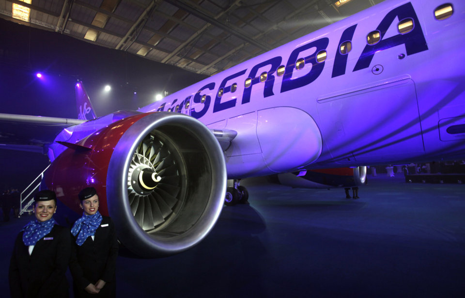 """Photo - New cabin crew members stand by the first Airbus A319-100 aircraft in Air Serbia livery parked in a hangar during the inauguration ceremony at Belgrade's Nikola Tesla Airport, Serbia, Friday, Oct. 25, 2013. Officials say that Air Serbia, Balkan country's new national carrier partly owned by Etihad Airways, formally starts flying this weekend, spelling the end for the old loss-making JAT Airways. Air Serbia's chief manager Dane Kondic said Friday that the company's inaugural flight will take place on Saturday to Abu Dhabi, United Arab Emirates. He says that """"it is an important flight that will mark a crossroads."""" Kondic and Serbia's deputy prime minister Aleksandar Vucic unveiled at a ceremony at Belgrade's airport an Airbus A319 plane bearing a double-headed eagle logo in Serbia's national, red, white and blue colors. Vucic says Air Serbia hopes to become the leading regional airline. (AP Photo/Darko Vojinovic)"""