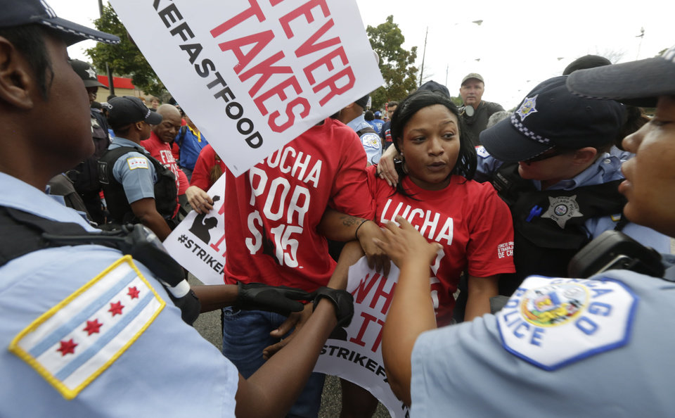 Photo - Chicago police remove protesters from the middle of 87th street between a McDonald's and a Burger King on Chicago's south side as labor organizers escalate their campaign to unionize the industry's workers, Thursday, Sept. 4, 2014. Police detained several protesters in cities nationwide Thursday as they blocked traffic in the latest attempt to escalate their efforts to get McDonald's, Burger King and other fast-food companies to pay their employees at least $15 an hour. (AP Photo/M. Spencer Green)