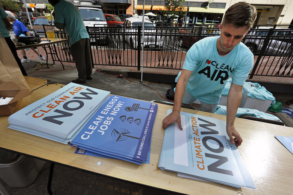 Photo - Sierra Club volunteer Alex Burke organizes signs to hand out near the local Environmental Protection Agency offices, on the first of two days of public hearings held by the EPA on President Barack Obama's plan to cut carbon dioxide emissions by 30 percent by 2030, in Denver, Tuesday, July 29, 2014. In hearings, hundreds of people across the country are telling the EPA its new rules for power-plant pollution either go too far or not far enough. (AP Photo/Brennan Linsley)