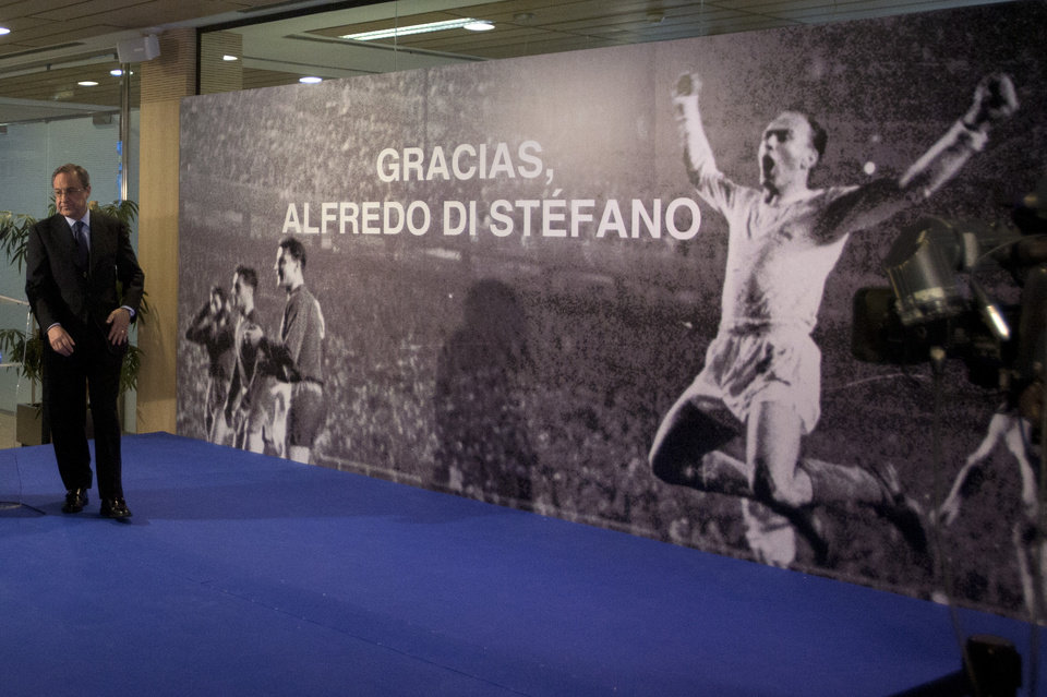 Photo - Real Madrid's President Florentino Perez ends his speech in front of a poster of Alfredo Di Stefano in the Santiago Bernabeu stadium in Madrid, Spain, Monday, July 7, 2014 after football great Alfredo Di Stefano died. He was 88. The former Argentina forward was hospitalized on Saturday after a heart attack. He had been in a coma since at Gregorio Maranon hospital in the Spanish capital where he passed away. Di Stefano helped Madrid win five straight European Champions Cups from 1956-60 and eight Spanish league titles. He was voted European player of the year in 1957 and 1959. (AP Photo/Paul White)