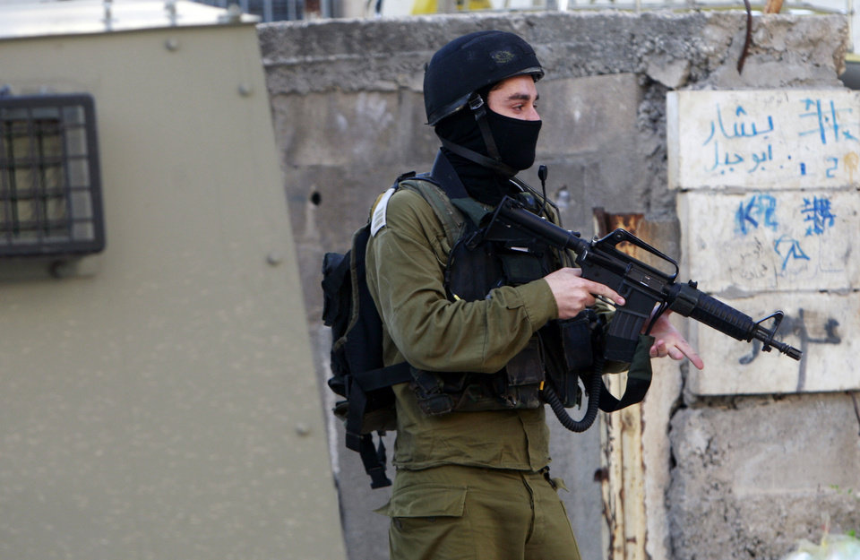 Photo - An Israeli army soldier takes a position during clashes with Palestinians in the early morning in the West Bank city of Jenin, Wednesday, July 2, 2014. Tensions have mounted between Israel and the Palestinians after the bodies of three Israeli teens were found in the West Bank more than two weeks after they went missing. (AP Photo/Mohammed Ballas)