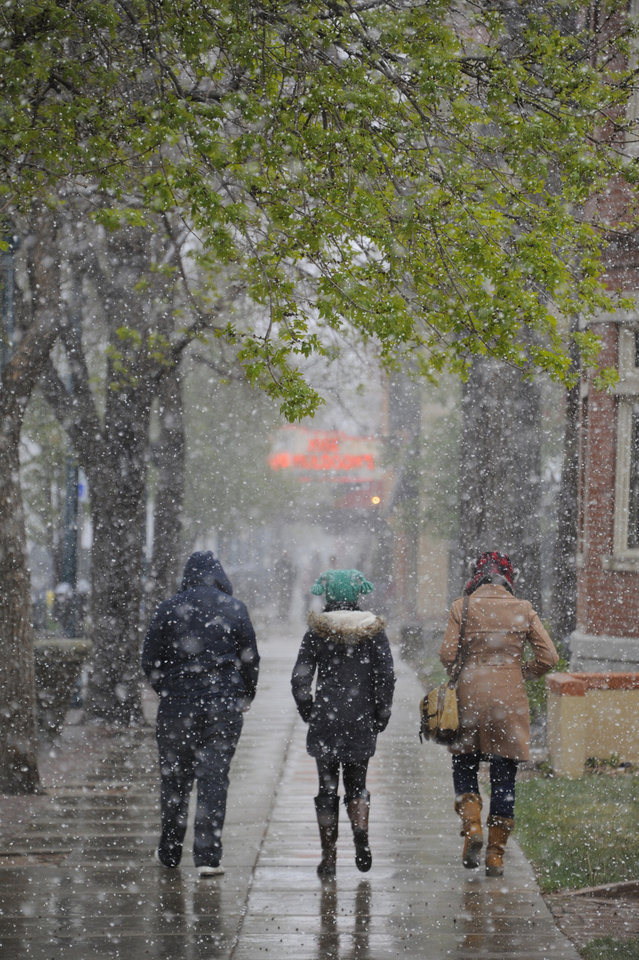 Photo - Pedestrians in downtown Colorado Springs, Colo. Sunday afternoon, May 11, 2014, as a spring snowstorm hits the Pikes Peak region. (AP Photo/The Gazette, Mark Reis)