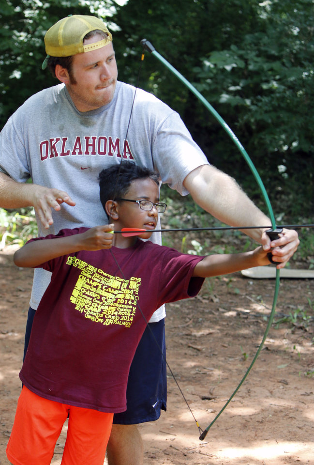 Eight year old Jordyn Harris gets instruction in archery from counselor Colin McCartney during Shiloh Camp, a Christian day camp in north Oklahoma City, OK, Tuesday, June 17, 2014,  Photo by Paul Hellstern, The Oklahoman