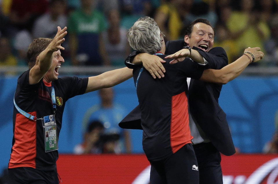 Photo - Belgium's head coach Marc Wilmots, right,  celebrates with his staff after the World Cup round of 16 soccer match between Belgium and the USA at the Arena Fonte Nova in Salvador, Brazil, Tuesday, July 1, 2014. Belgium won the match 2-1 after extra-time. (AP Photo/Matt Dunham)