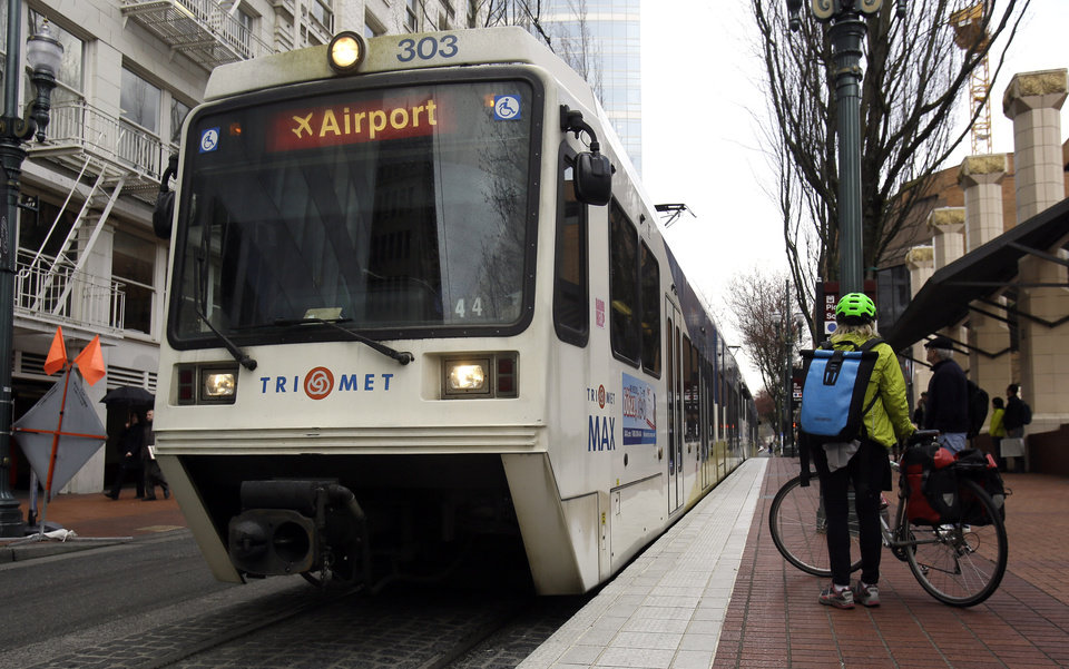 Photo - A bicyclists waits to board an incoming MAX train in Portland, Ore., Monday, March 10, 2014. While use of buses, trains and subways is on the rise in many cities across America, ridership in the Portland area's much touted system has actually fallen off, according to new data released by the American Public Transportation Association. (AP Photo/Don Ryan)