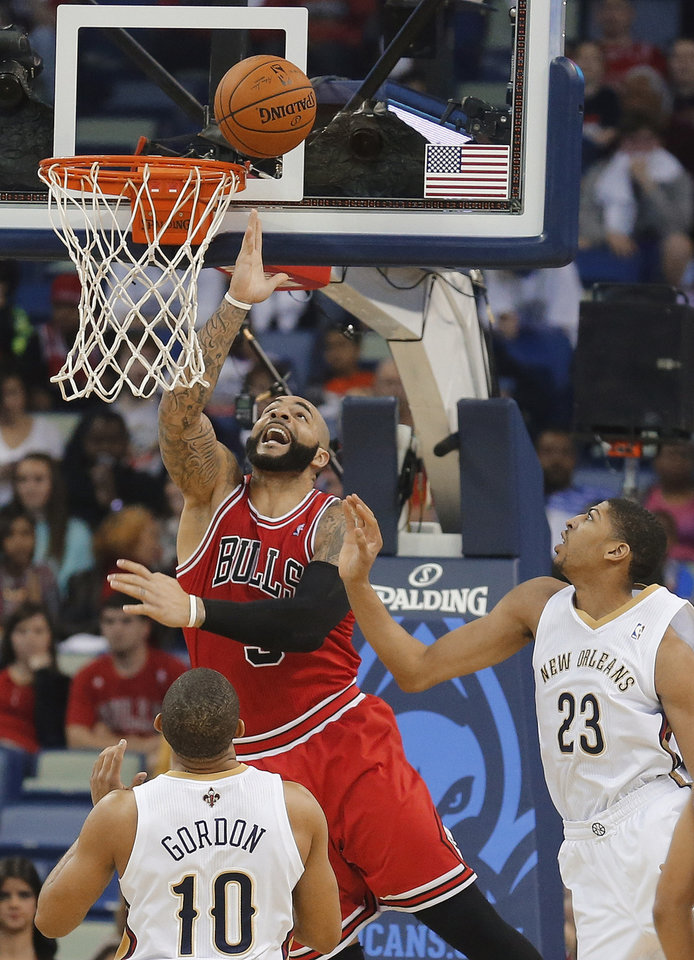 Photo - Chicago Bulls forward Carlos Boozer (5) goes to the basket as New Orleans Pelicans forward Anthony Davis (23) and guard Eric Gordon (10) watch during the first half of an NBA basketball game in New Orleans, Saturday, Feb. 1, 2014. (AP Photo/Bill Haber)