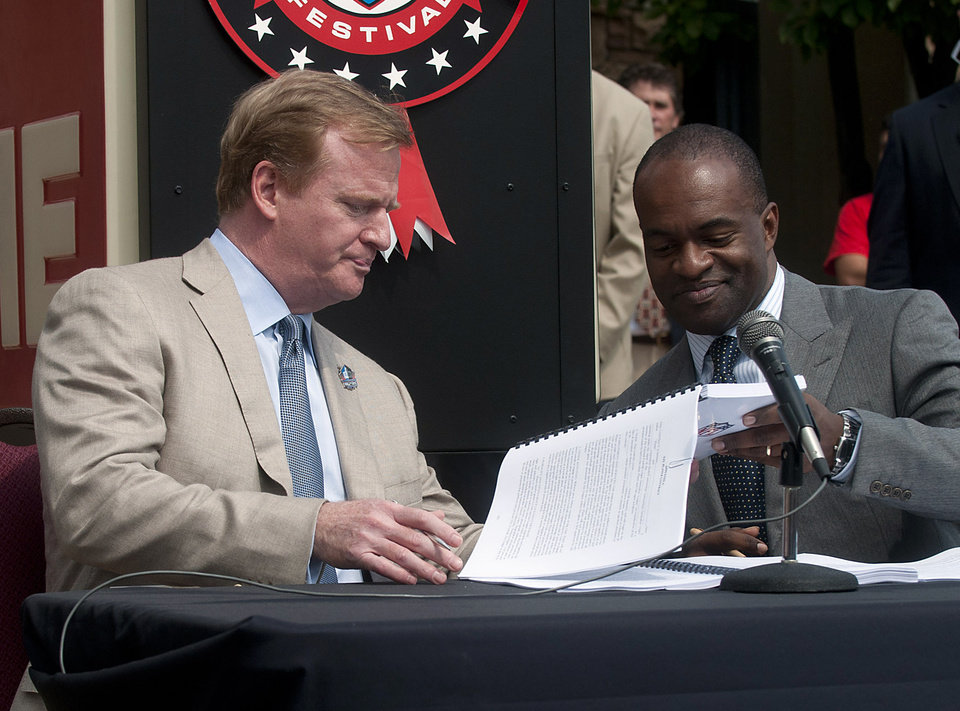 Photo -   FILE - In this Aug. 5, 2011, file photo, NFL Commissioner Roger Goodell, left, and NFLPA Executive Director Demaurice Smith exchange papers as they sign their collective bargaining agreement at the Pro Football Hall of Fame in Canton, Ohio. The NFL Players Association has filed a complaint Wednesday, May 23, 2012, in federal court accusing the league of colluding to impose a secret salary cap during the uncapped 2010 season. (AP Photo/Phil Long, File)