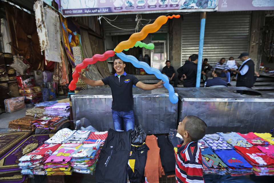 Photo - A Palestinian vendor plays with balloons at the market in the Jebaliya refugee camp, northern Gaza Strip, Sunday, July 27, 2014. During normal times, families in Gaza would be busy now with preparations for Eid al-Fitr, the three-day holiday marking the end of the Muslim fasting month of Ramadan. Traditionally, children get new clothes, shoes and haircuts, and families visit each other. In the outdoor market, vendors set up stands with clothes and shoes, but said business was slow. (AP Photo/Lefteris Pitarakis)