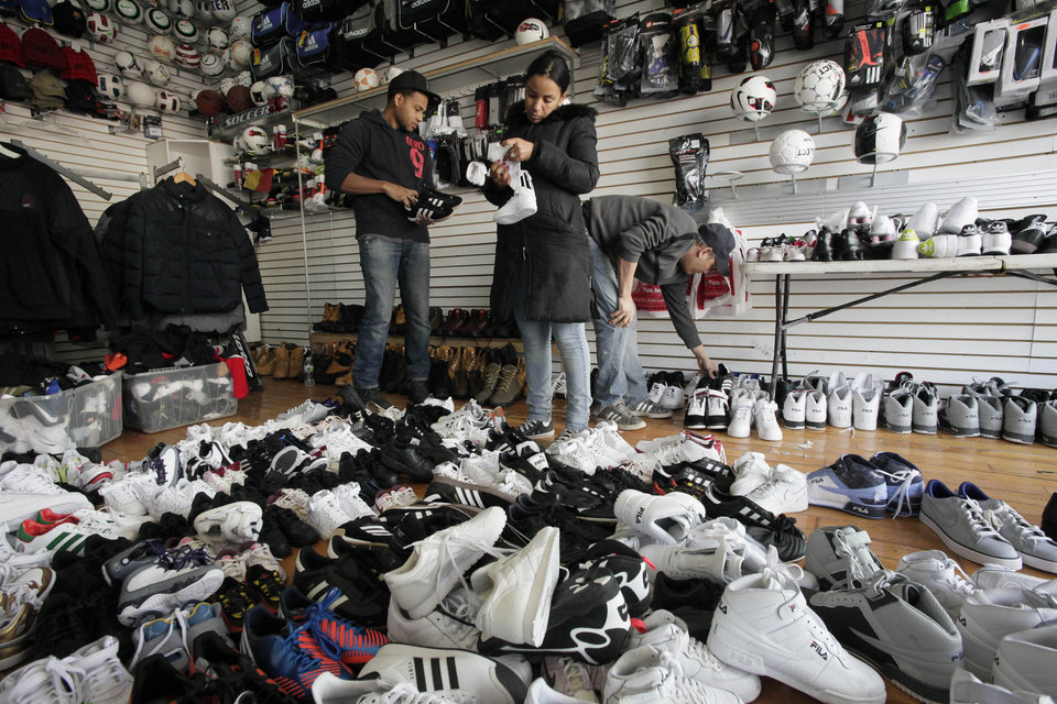 A shopper, center, picks through water-damaged shoes in Sneaker Town, Tuesday, Nov. 6, 2012 in the Coney Island section of New York. The store is clearing out its inventory damaged by Superstorm Sandy. (AP Photo/Mark Lennihan) ORG XMIT: NYML104