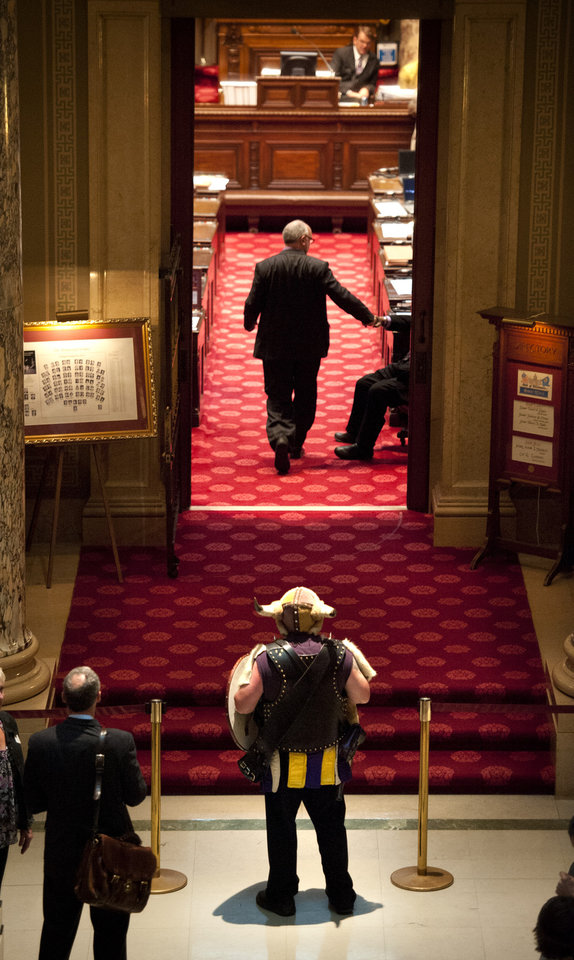 Photo -   Greg Hanson, who goes by the name Sir Odin, looks into the state Senate chamber, emptied for a two-hour recess, before the Senate came back to debate the Minnesota Vikings stadium bill Tuesday, May 8, 2012, in St. Paul, Minn. (AP Photo/Star Tribune, Glen Stubbe) ST. PAUL OUT MINNEAPOLIS-AREA TV OUT MAGS OUT