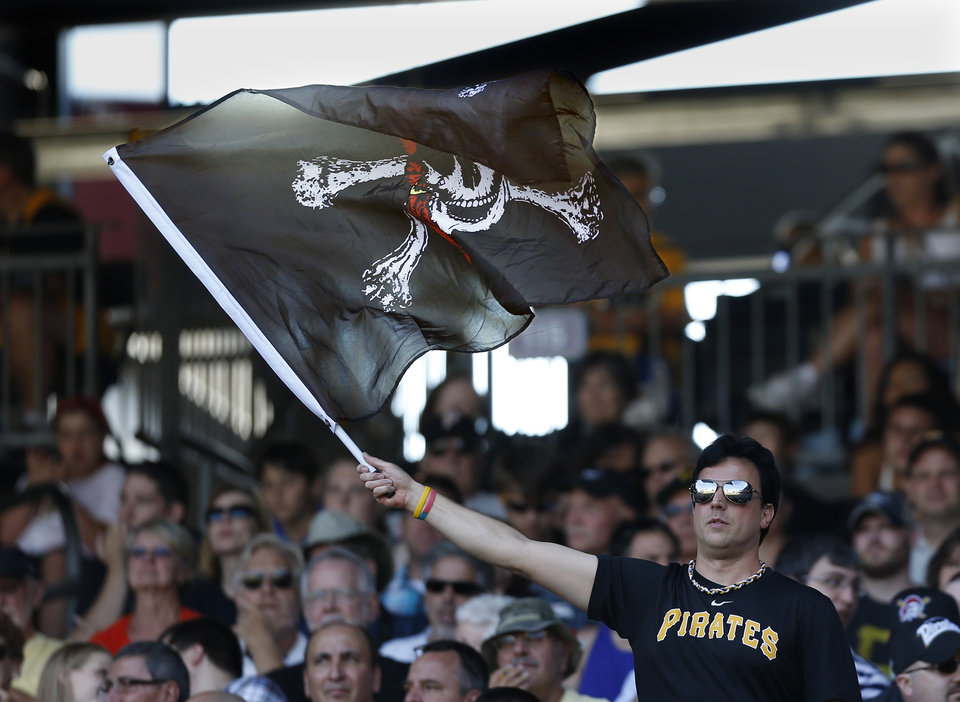 Photo - In this photo from Sunday, June 30, 2013, A Pittsburgh Pirates fan waves a