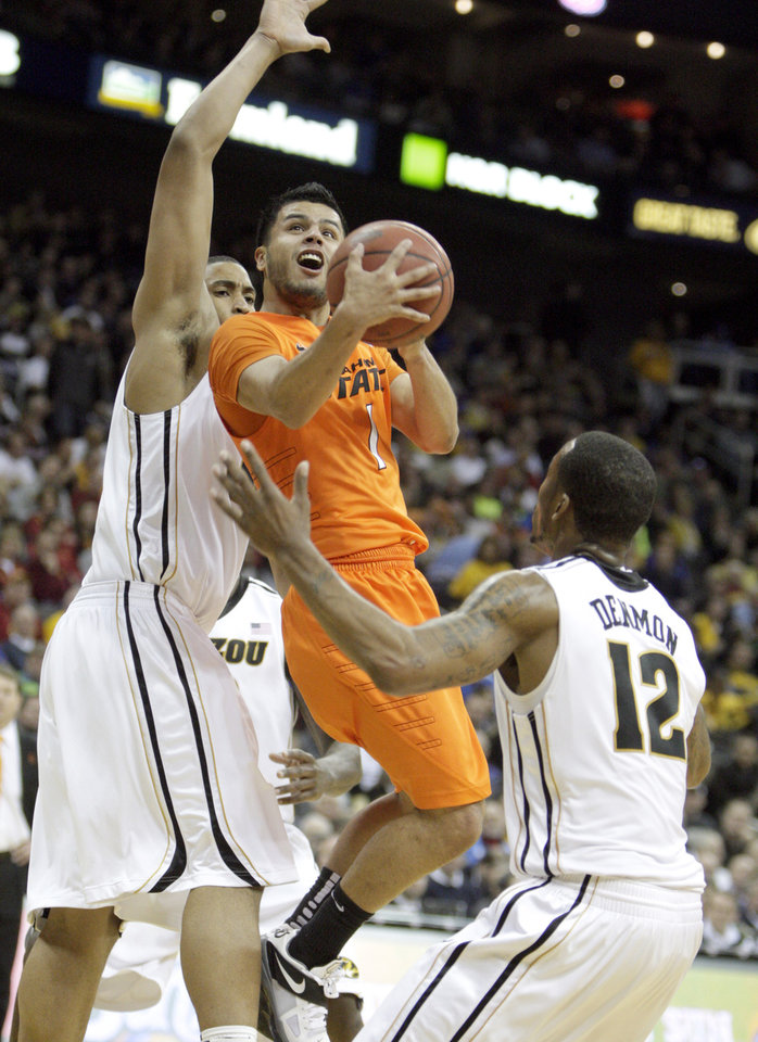 Oklahoma's Cezar Guerrero (1) shoots in between Missouri's Steve Moore (32) and Marcus Denmon (12) during the Big 12 tournament men's basketball game between the Oklahoma State Cowboys and Missouri Tigers the Sprint Center, Thursday, March 8, 2012. Photo by Sarah Phipps, The Oklahoman