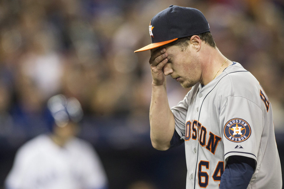 Photo - Houston Astros starting pitcher Lucas Harrell returns to the dugout after the third inning of a baseball game against the Toronto Blue Jays on Wednesday, April 9, 2014, in Toronto. (AP Photo/The Canadian Press, Chris Young)