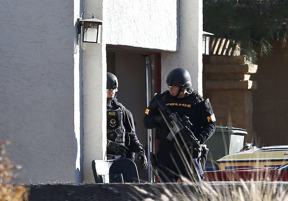 Photo - Members of the Phoenix Police Department SWAT team exit the garage at the home of a suspected gunman who opened fire at a Phoenix office building, wounding three people, one of them critically, and setting off a manhunt that led police to surround his house for several hours before they discovered he wasn't there, Wednesday, Jan. 30, 2013, in Phoenix.  Authorities believe there was only one shooter, but have not identified him or a possible motive for the shooting. They don't believe the midmorning shooting at the complex was a random act. (AP Photo/Ross D. Franklin)