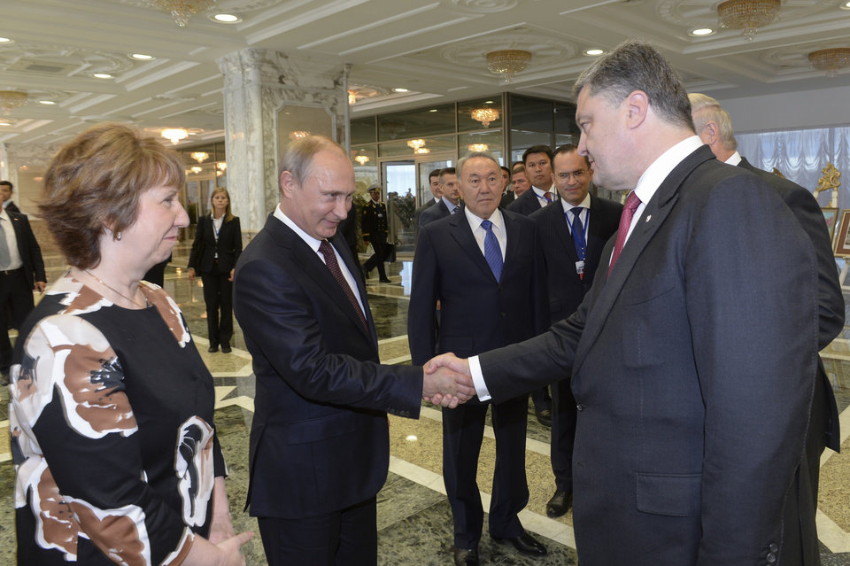 Photo - Russian President Vladimir Putin, second left, shakes hands with Ukrainian President Petro Poroshenko, right, as EU foreign policy chief Catherine Ashton, left, and Kazakh President Nursultan Nazarbayev, center, watch, prior to their talks after after posing for a photo in Minsk, Belarus, Tuesday, Aug. 26, 2014. Leaders of Russia, Belarus, two other former Soviet republics as well as top EU officials are meeting in Minsk, Belarus, for a highly anticipated summit to discuss the crisis in Ukraine which has left more than 2,000 dead and displaced over 300,000 people. (AP Photo/Kazakh Presidential Press Service, Sergei Bondarenko, Pool)