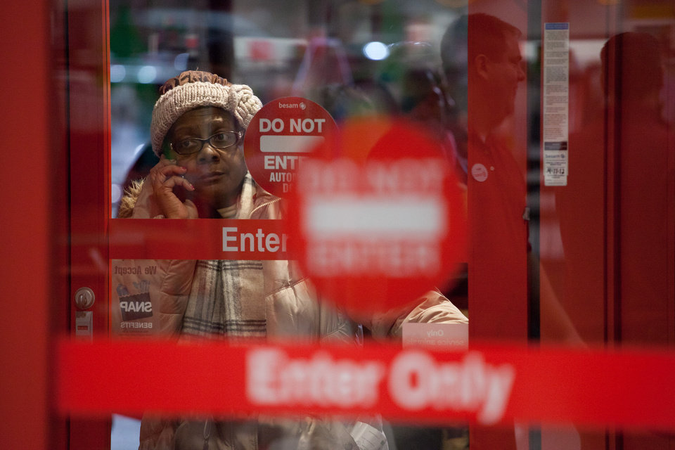 A woman talks on her cellphone next to the entrance of Target just minutes before the start of a Black Friday sales event in Flint, Mich. on Thursday, Nov. 22, 2012.Black Friday, the day when retailers traditionally turn a profit for the year, actually got a jump start this year as many stores opened just as families were finishing up Thanksgiving dinner. Stores are experimenting with ways to compete with online rivals like Amazon.com that can offer holiday shopping deals at any time and on any day. (AP Photo/The Flint Journal, Griffin Moores)