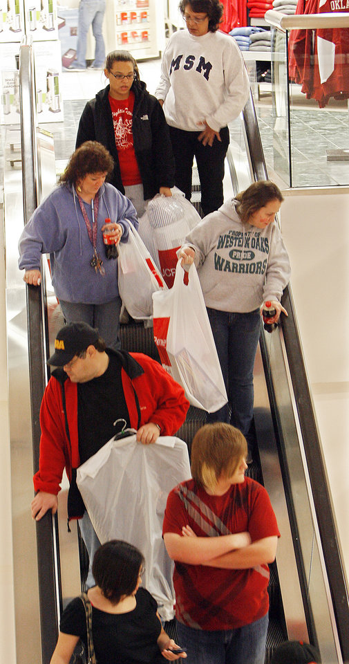 Photo - Black Friday. Shoppers ride the escalator with their packages at the  J.C. Penney's in Penn Square Mall , Friday, November 27, 2009. The doors opened at 4:00 A.M. By David McDaniel, The Oklahoman.
