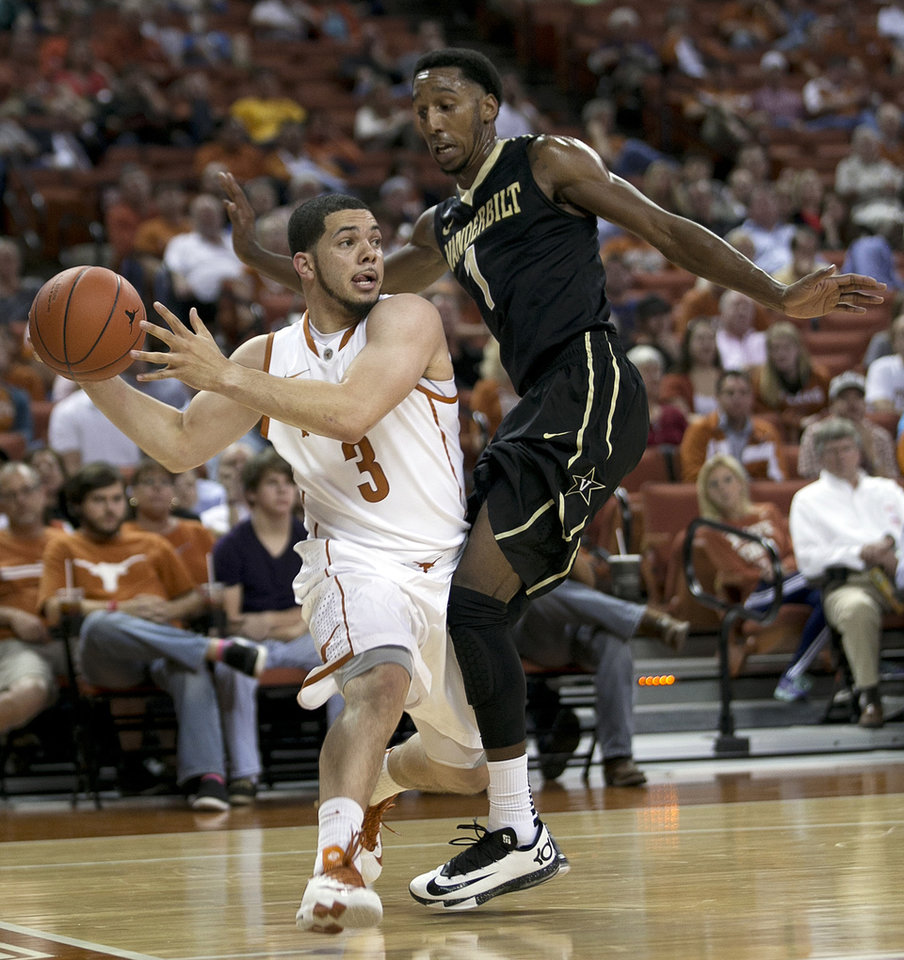 Texas's Javan Felix, left, passes around Vanderbilt's Eric McClellan during the first half of an NCAA college basketball game in Austin, Texas, on Monday, Dec. 2, 2013. (AP Photo/Austin American-Statesman, Deborah Cannon)