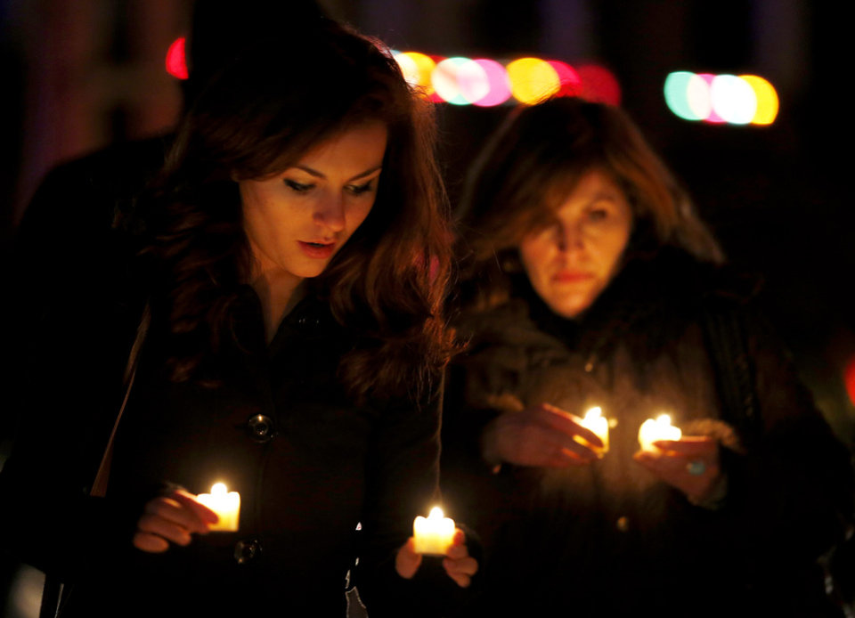 Photo - Katy Caulfield, left, and her mother, Irene Caufield, hold candles to place at a makeshift memorial near the elementary school where a day earlier a gunman opened fire, Saturday, Dec. 15, 2012, in Newtown, Conn. The man, who died from a self-inflicted wound, allegedly killed his mother at their home and then opened fire Friday inside the Sandy Hook Elementary school, massacring 26 people, including 20 children. (AP Photo/Julio Cortez) ORG XMIT: CTJC142
