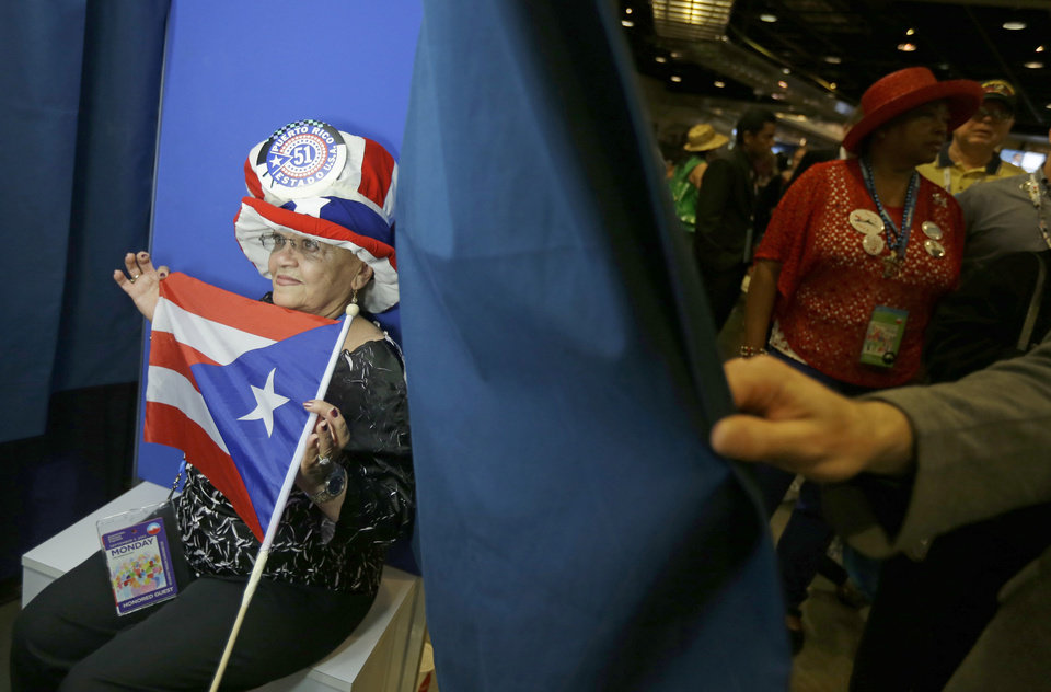 Photo - New York delegate Julia Rodriguez poses with Puerto Rico flag in a photo booth at the Democratic National Convention in Charlotte, N.C., on Wednesday, Sept. 5, 2012. (AP Photo/David Goldman)  ORG XMIT: DNC757