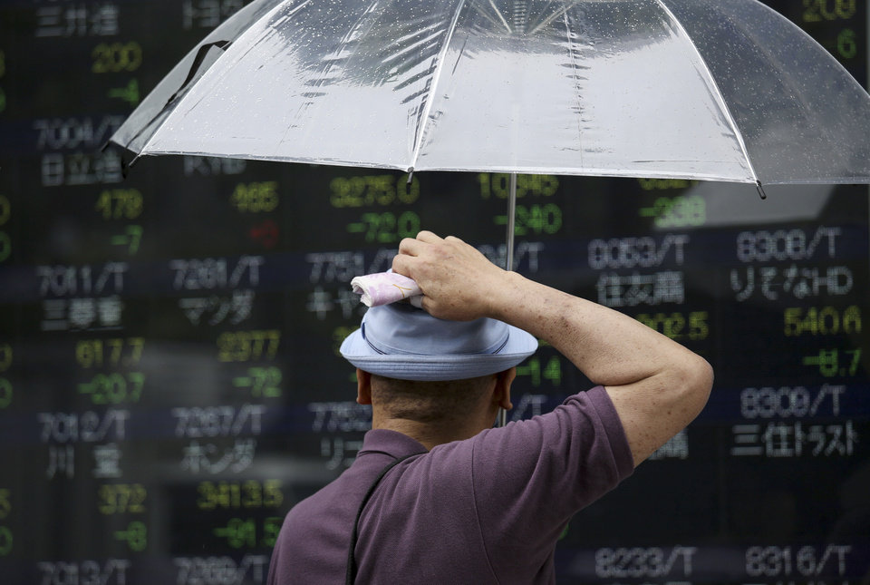 Photo - A man scratches his head as he looks at an electronic stock board of a securities firm in Tokyo as the 225-issue Nikkei Stock Average dived 454.00 points, or 2.98 percent, and finished at 14,778.37, hitting a two-month low Friday, Aug. 8, 2014. Asian stocks sank Friday as jitters over the crises in Iraq and Ukraine escalated but Chinese stocks rose after trade figures showed surprisingly strong growth in exports. (AP Photo/Eugene Hoshiko)