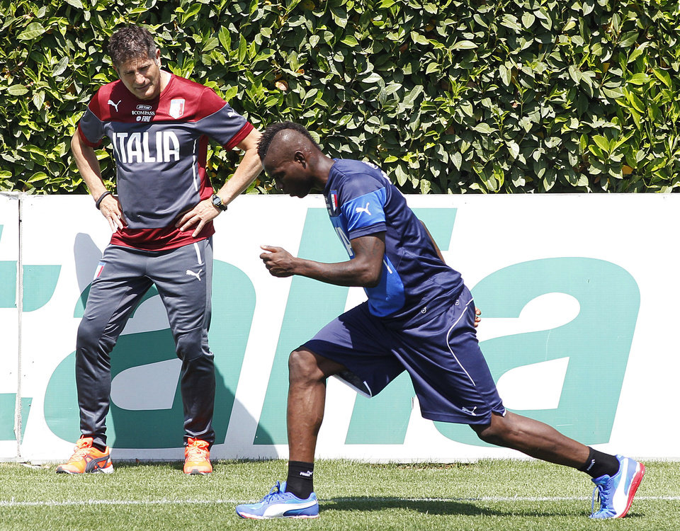 Photo - Italy's Mario Balotelli, right, warms up during a training session in Coverciano training complex, in Florence, Italy, Wednesday, May 21, 2014. The Azzurri will train for three days this week then resume full-time preparation next Monday. In Brazil, Italy is in Group D with England, Uruguay and Costa Rica. (AP Photo/Fabrizio Giovannozzi)