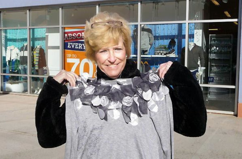 Norma Creech, of Moore, shows off a long-desired blouse she found Friday at the Disney Store at The Outlet Shoppes at Oklahoma City.