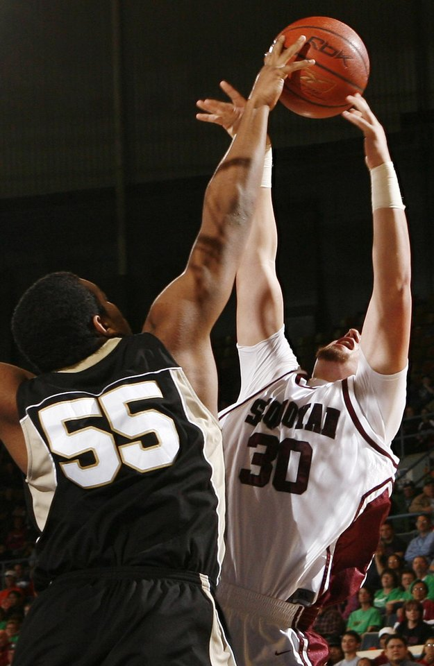 Photo - Okemah's Chris Boyd (55) blocks the shot of Jarrett Travis (30) of Sequoyah-Tahlequah during the 3A boys semifinal game between Okemah and Sequoyah-Tahlequah in the Oklahoma High School Basketball Championships at State Fair Arena in Oklahoma City, Friday, March 13, 2009. Okemah won to advance to the finals. PHOTO BY NATE BILLINGS, THE OKLAHOMAN